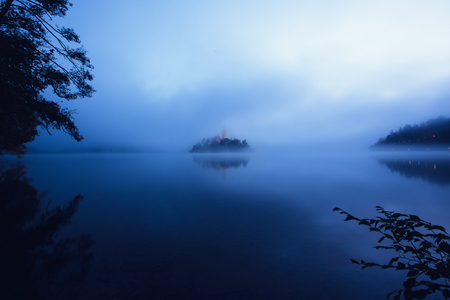 Panorama view of the famous island with old church in the city of Bled Blejsko jezero. Dreamy scene with mist and cold colors. Slovenia, Europe