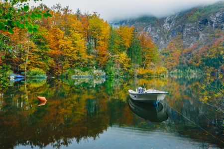 Autumnal scenic view of boats on the Bohinj lake surrounded by colorful forest. Slovenia, Europe, Triglav National Park