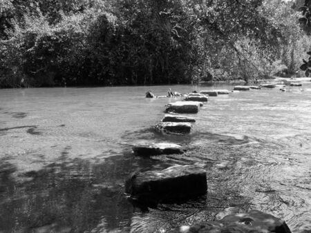 A black and white picture of stones placed in the water at Bull Creek in Austin TX. photo
