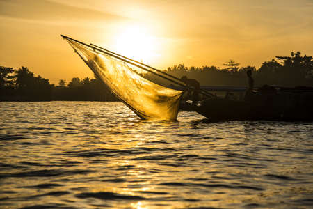 fishnet: Fishing boat with fishnet on the Mekong River at sunrise. Can Tho Vietnam.