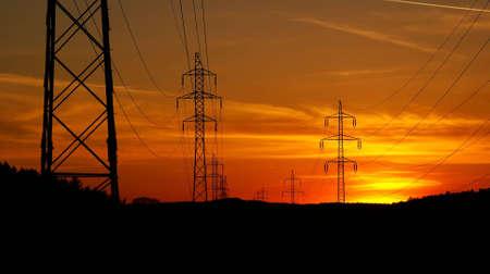 over voltage: High voltage electricity pylon over sunset