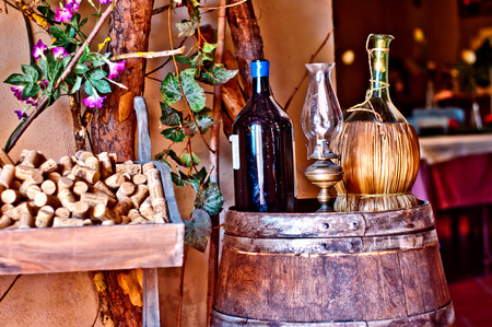wine bottles, with bottle of olive oil, resting on an oak barrel cellar in a typical Italian photo