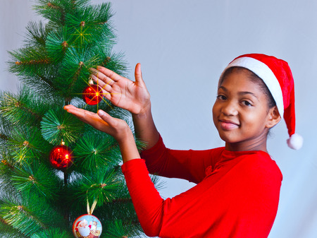 black girl dressed as Santa Claus who decorate the Christmas tree with lights, balls and candles 免版税图像