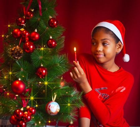 latin american ethnicity: black girl dressed as Santa Claus who decorate the Christmas tree with lights, balls and candles Stock Photo