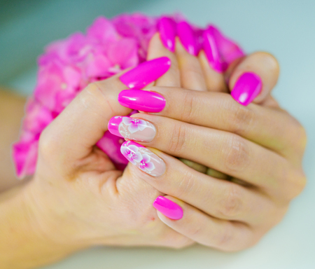 nudism: colored nails with pink flowers decorations to celebrate the spring and summer Stock Photo
