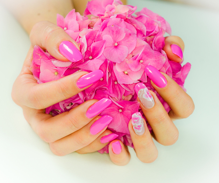 colored nails with pink flowers decorations to celebrate the spring and summer Stock Photo