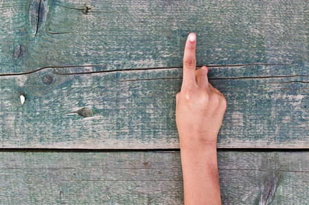 four in one: a hand tells us the right number, one, two, three, four, five out of an aged wooden table