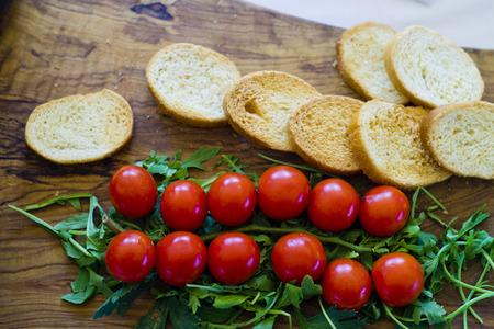 carnes y verduras: Un delicioso aperitivo con tomates cherry, rúcula y bruschetta