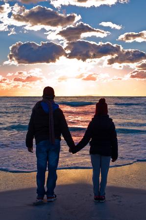 altruismo: dos personas viendo la puesta de sol que se va a dormir en el mar