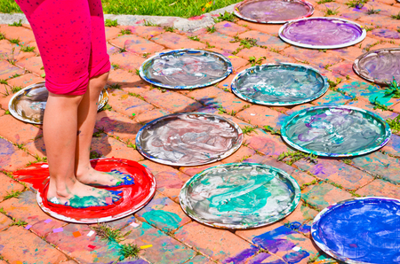 tempera: children playing making colorful designs with their feet immersed in the colorful tempera Stock Photo