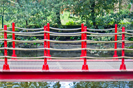 collodi: pedestrian bridge built in art wooden, red railing and hemp ropes in the park of Pinocchio in Italy