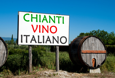 Traditional wooden barrel with a billboard that advertises the sale of wine in the Tuscan countryside Stock Photo