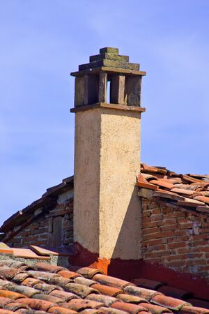 proprietary: chimney in plaster and brick, on roof tiles of traditional building