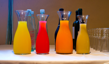 jugs of fresh juice of oranges, lemon, pineapple, peach, apricot, angular, papaya resting on a table for a party