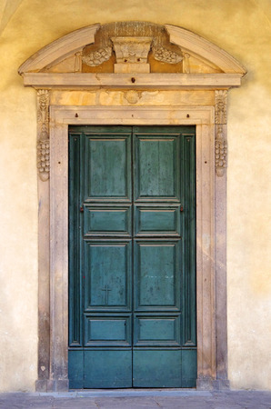 mediterranian style: a cross decorates the door painted green and very consumanta of an ancient church