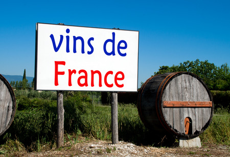 advertises: Traditional wooden barrel with a billboard that advertises the sale of wine in the French countryside