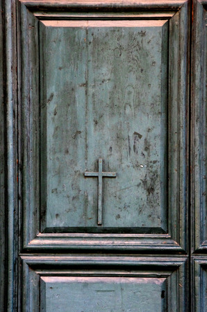 mediterranian style: ancient door of the historic church decorated with a cross