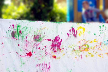 colored dye: children playing making colorful designs with hands dipped in colored dye