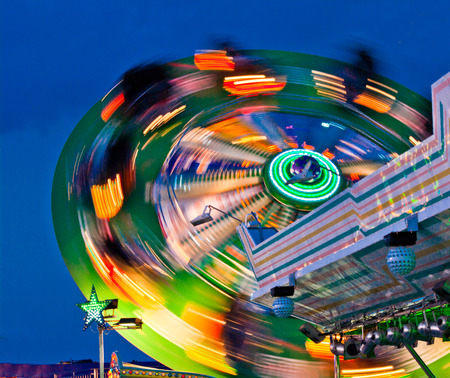 turns: the carousel that turns the night of carnival colored leaves trails in the sky that darkens Stock Photo