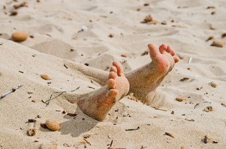 working stiff: two feet on the beach in rigor mortis protrude from the sand