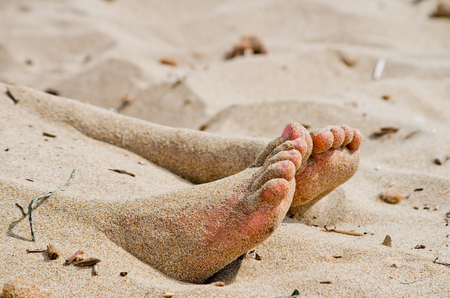 two feet of a girl come out of the hot sand to the game and to improve blood circulation