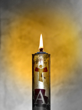 paschal candle with its light comes from the Holy Spirit and always accompanies the body of Christ Фото со стока
