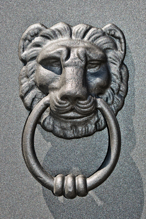 door knocker with bright iron lion in the sun
