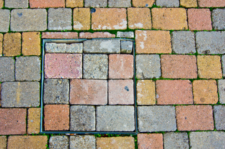 modular rhythm: paving pattern stone blocks with shape and color irregular with manhole