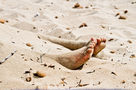 the feet of a corpse that protrude from the sand