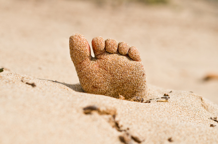 rigor: two feet on the beach in rigor mortis protrude from the sand