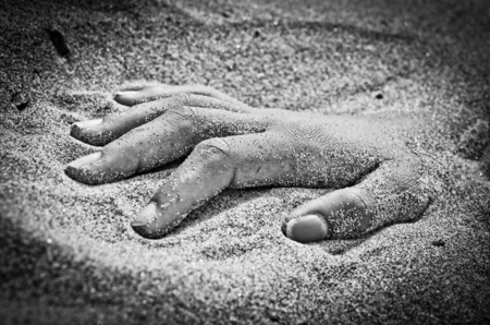 rigor: on the beach hand in rigor mortis protruding from the sand