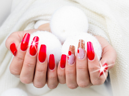 nails decorated with red, Christmas decorations and golden hues to celebrate your fantastic Christmas and New Year's party Archivio Fotografico