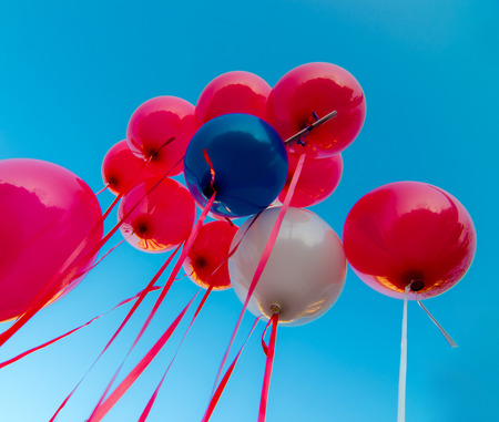 gamete: many colorful balloons launched from the children happy flying in the blue sky