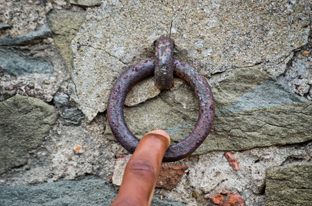 acts: finger pulls an old rusty iron ring that acts as the bell of the old stone and brick wall