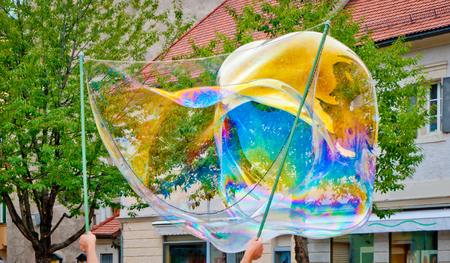 big soap bubble with a thousand colored reflections created by a juggler to make children happy Stock Photo