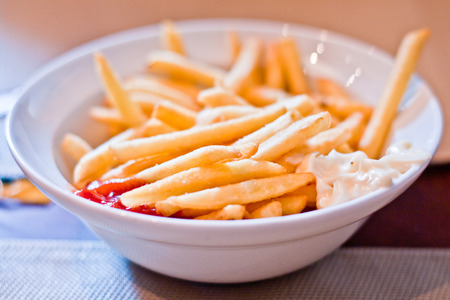triglycerides: plate of hot and fragrant fries with mayonnaise and ketchup