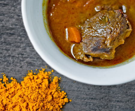 cup of tasty soup, hot and steaming with beef, vegetables, curry, turmeric and clove seeds Stock Photo