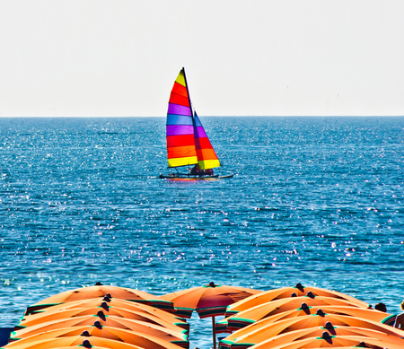 boat on the sea background with orange umbrellas in summer with blue sky