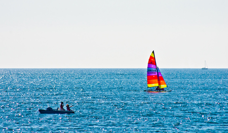 vacationers and bathers to the sea with a sailing boat colorful
