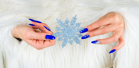 nails decorated with blue color and bright stars to celebrate Christmas and the last of the year