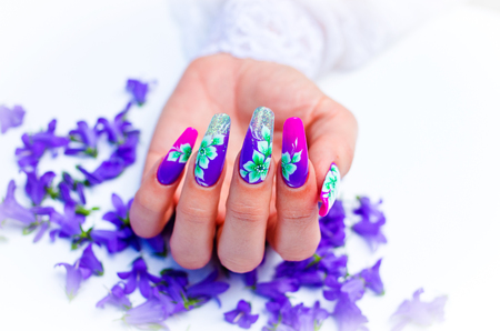 Hand with nails rebuilt and decorated with colorful flowers bring blue and white floral on white background, beautiful novelty for spring and summer