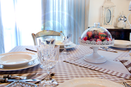 Table set for holidays or parties or for receiving guests with elegant dishes, cutlery, personalized napkins With the morning light coming in from the window