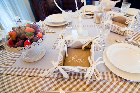 Table set for holidays or parties or for receiving guests with elegant dishes, cutlery, personalized napkins