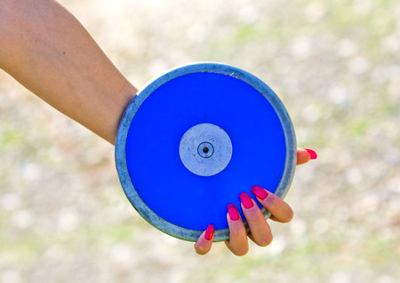 lanzamiento de disco: blue disc close to a hand with red fingernails ready to be launched Foto de archivo