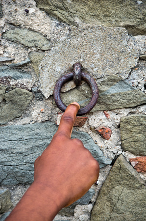 finger pulls an old rusty iron ring that acts as the bell of the old stone and brick wall