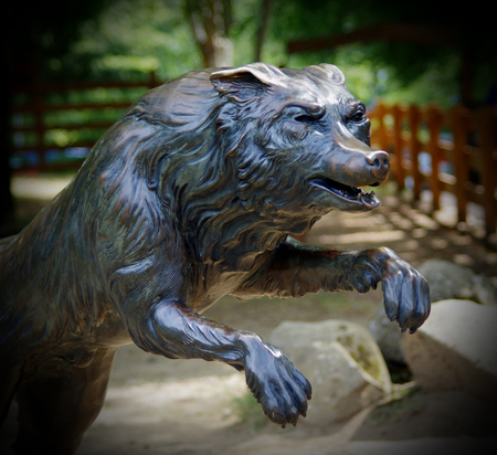Wolf statue in the park with trees, tourists, families and children