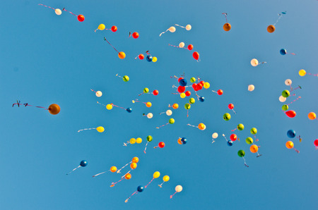 colorful balloons flying in the blue sky like so many colored sperm