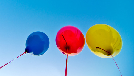 many colorful balloons launched from the children happy flying in the blue sky