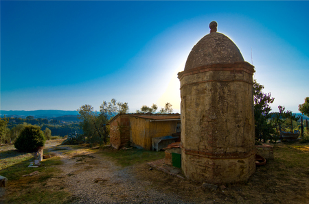 octogonal: sun rises behind the historic octagonal masonry well in the Tuscan countryside Foto de archivo
