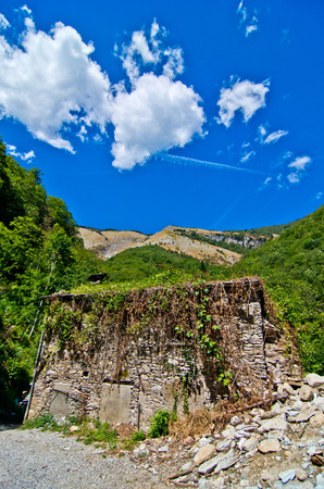 stone building collapsed due to the earthquake and flooded by plants under the blue sky Stock Photo
